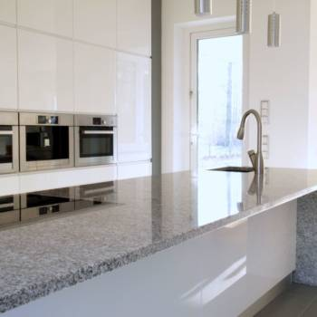 Minimalist modern kitchen with buil-in appliances and induction hob